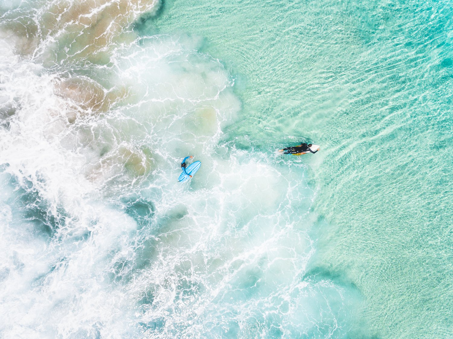 Aerial view of two surfers paddling in turquoise water and foam