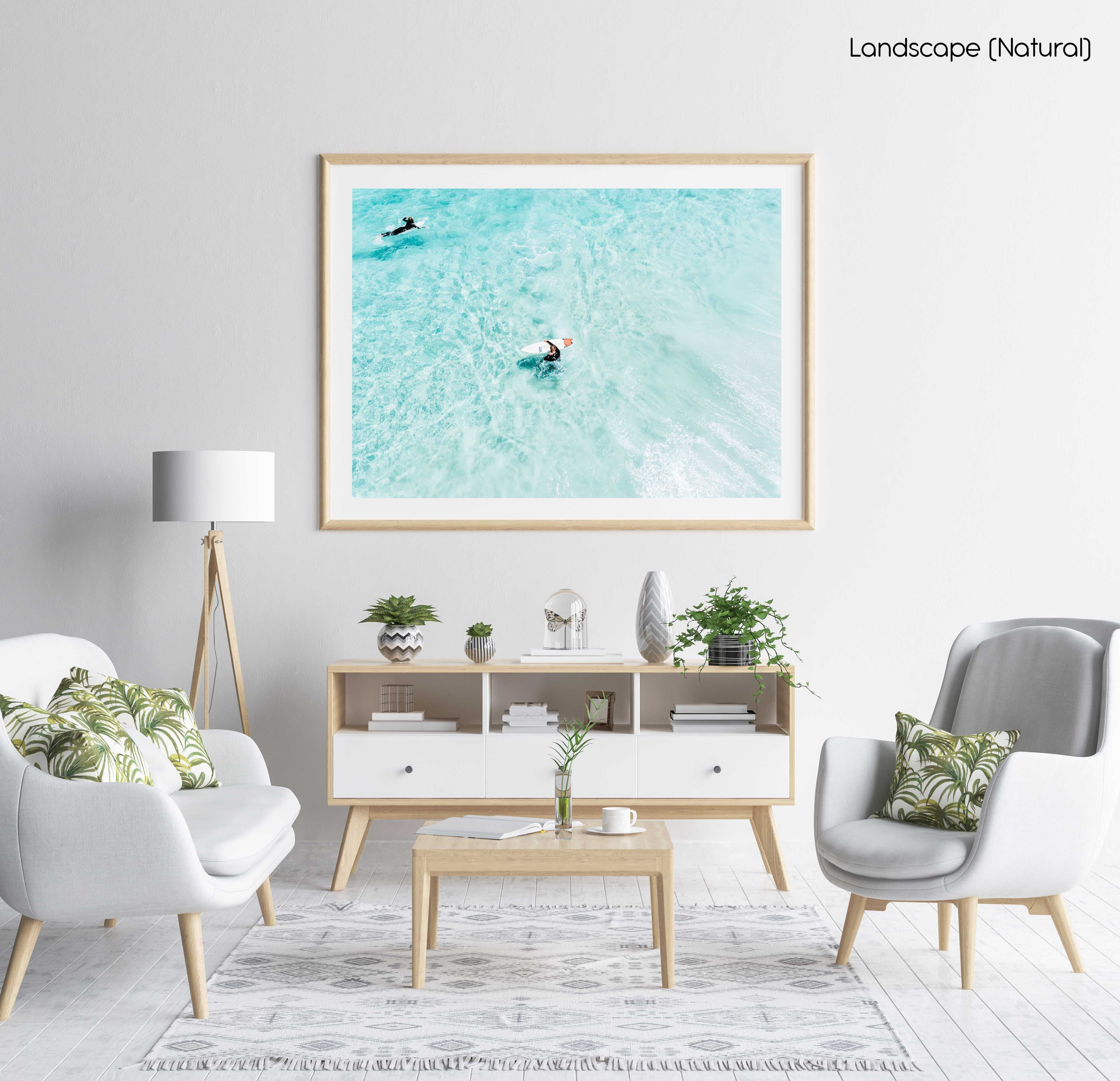 Surfers from above in light blue water in Cape Town in a natural fine art frame