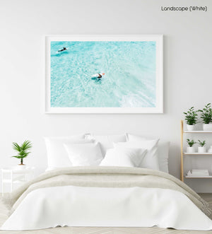 Surfers from above in light blue water in Cape Town in a white fine art frame
