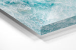 Light blue surfer paddling through foam from above in an acrylic/perspex frame