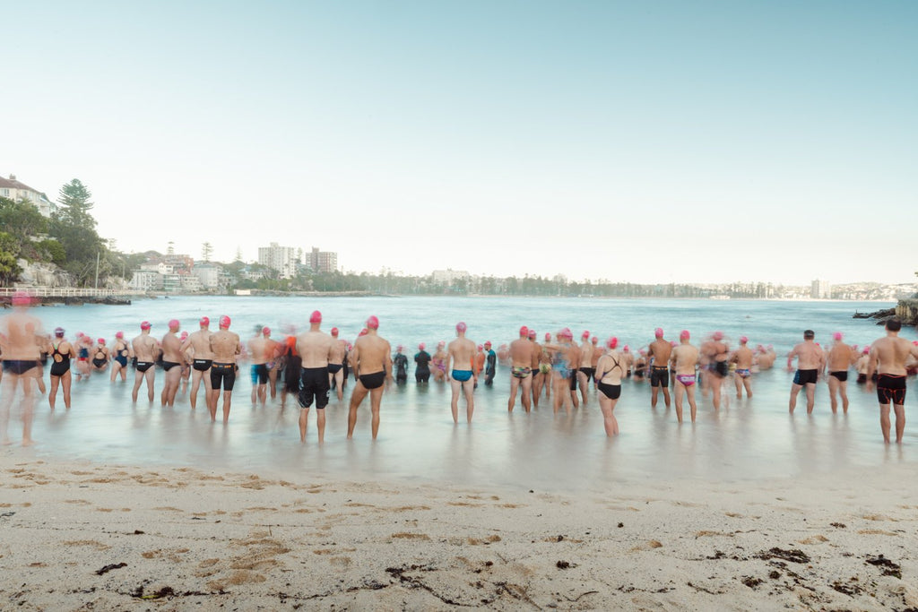 Lots of pink cap swimmers about to get in water at Shelly Beach Sydney