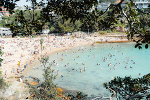 Crowded Shelly Beach swimmers in turquoise water on summers day