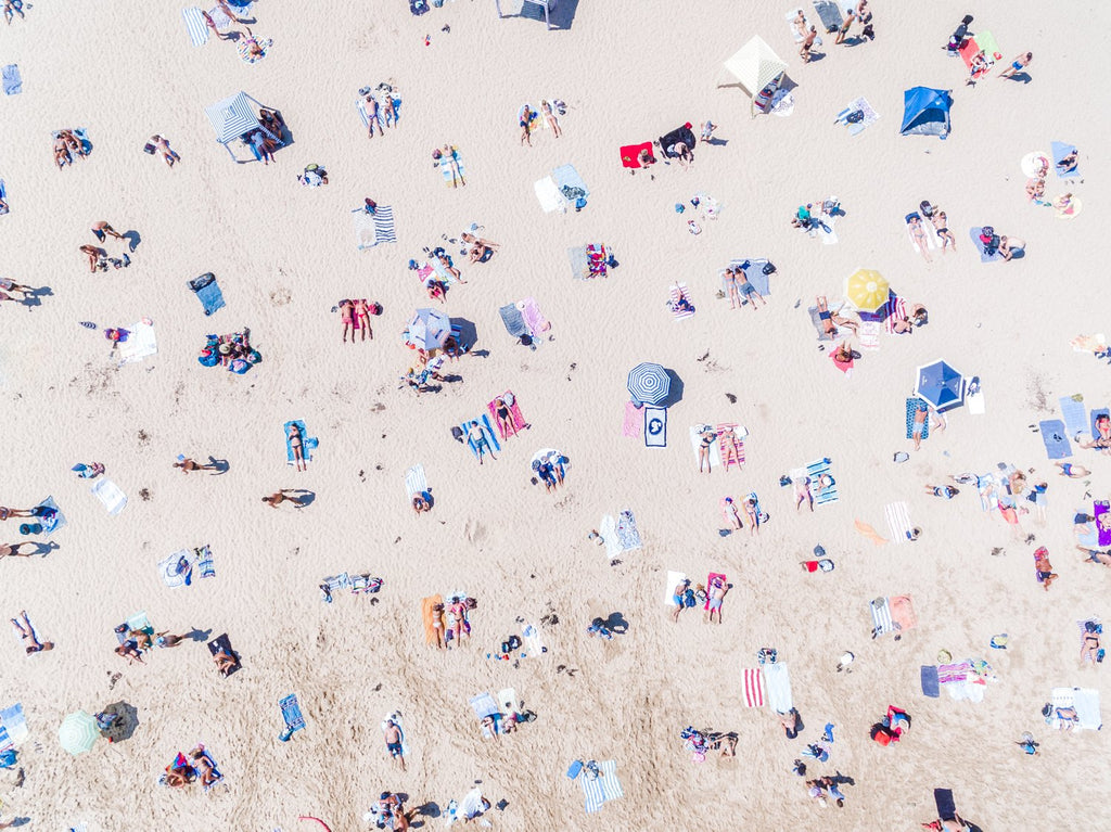 Aerial topdown of people tanning at the beach in Sydney