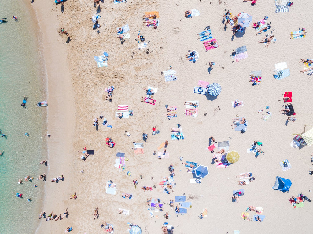 Aerial topdown of colorful people tanning by the sea at the beach in Sydney