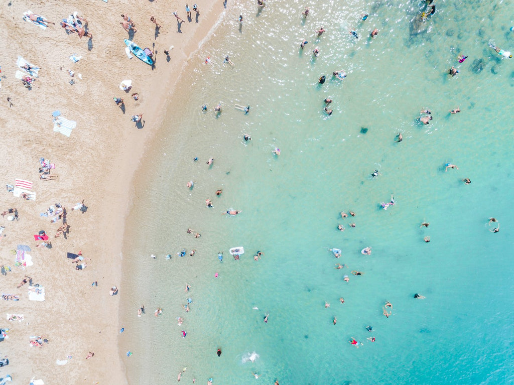 Aerial topdown of blue sea and people swimming at the beach in Sydney
