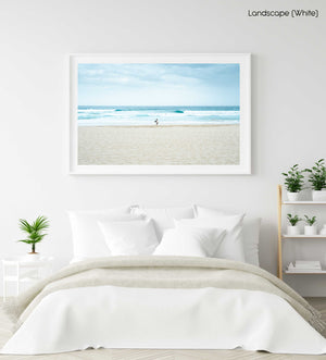 Man with surfboard looking out to blue waves along Manly Beach in Sydney in a white fine art frame