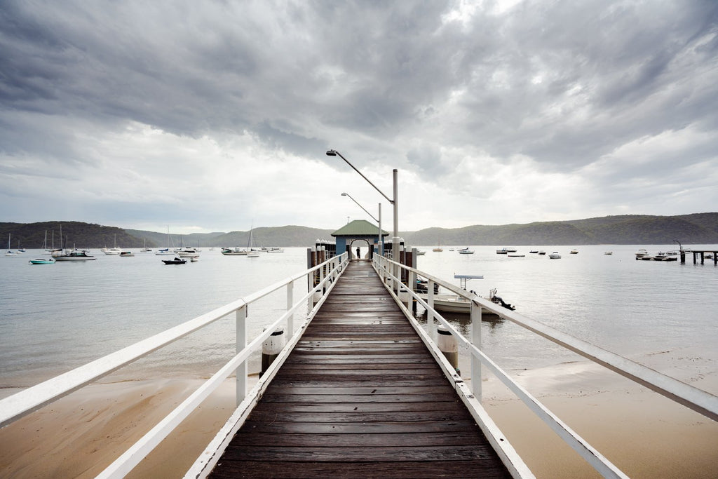 Moody clouds rolling towards boats and boardwalk in Sydney