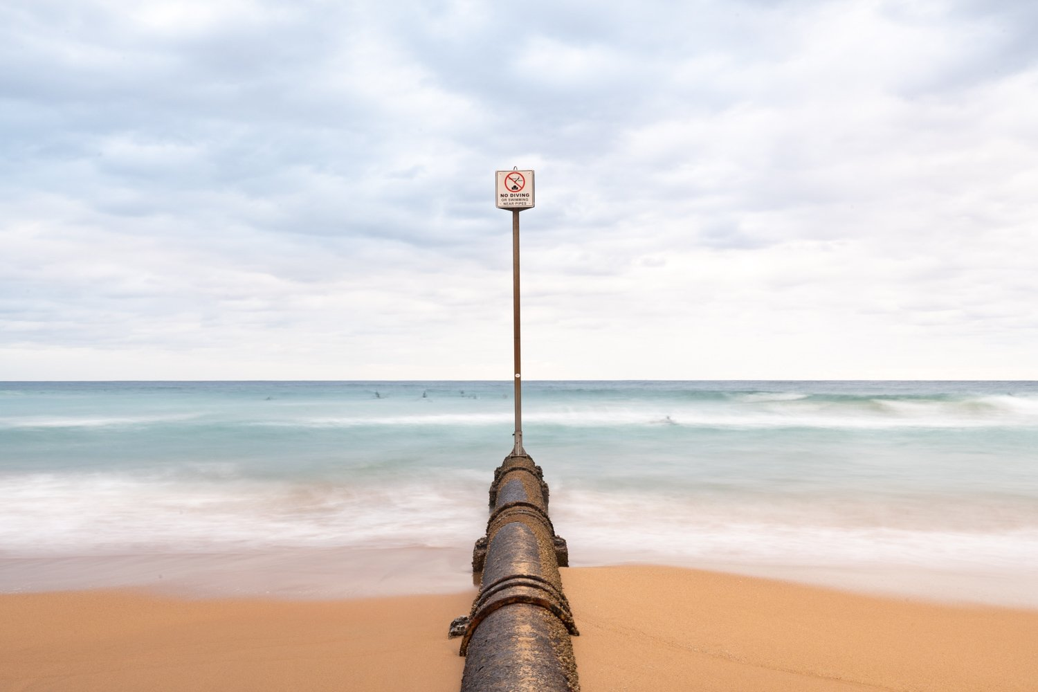 No diving sign and pipe in sea at Manly Beach NSW