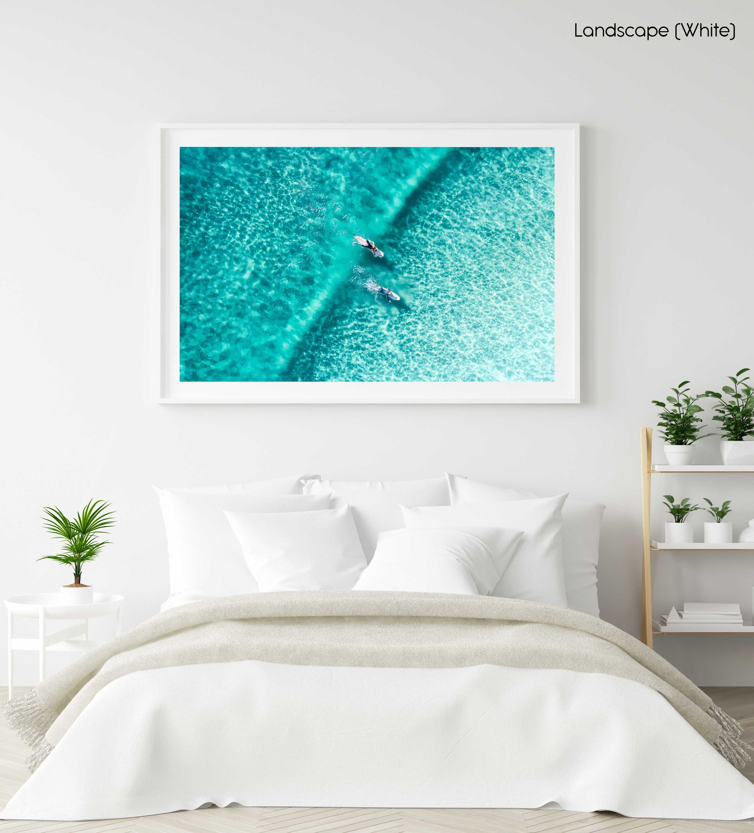 Two surfers paddling on one blue wave from aerial view in a white fine art frame
