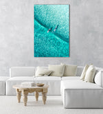 Two surfers paddling on one blue wave from aerial view in a natural fine art frame