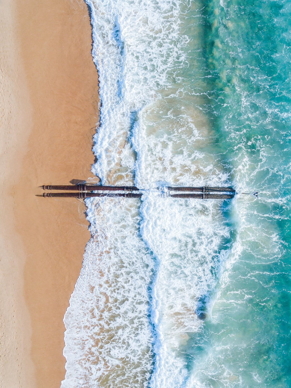 Aerial of beach pipes in ocean waves on Manly Beach Sydney