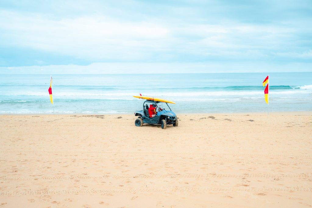 Lifesavers in a blue beach buggy with yellow board on roof in Monavale Beach Sydney