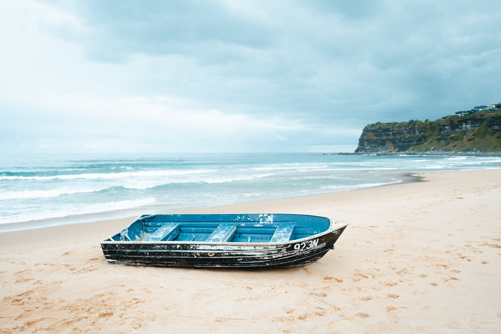 Stranded blue boat on northern beaches on cloudy day