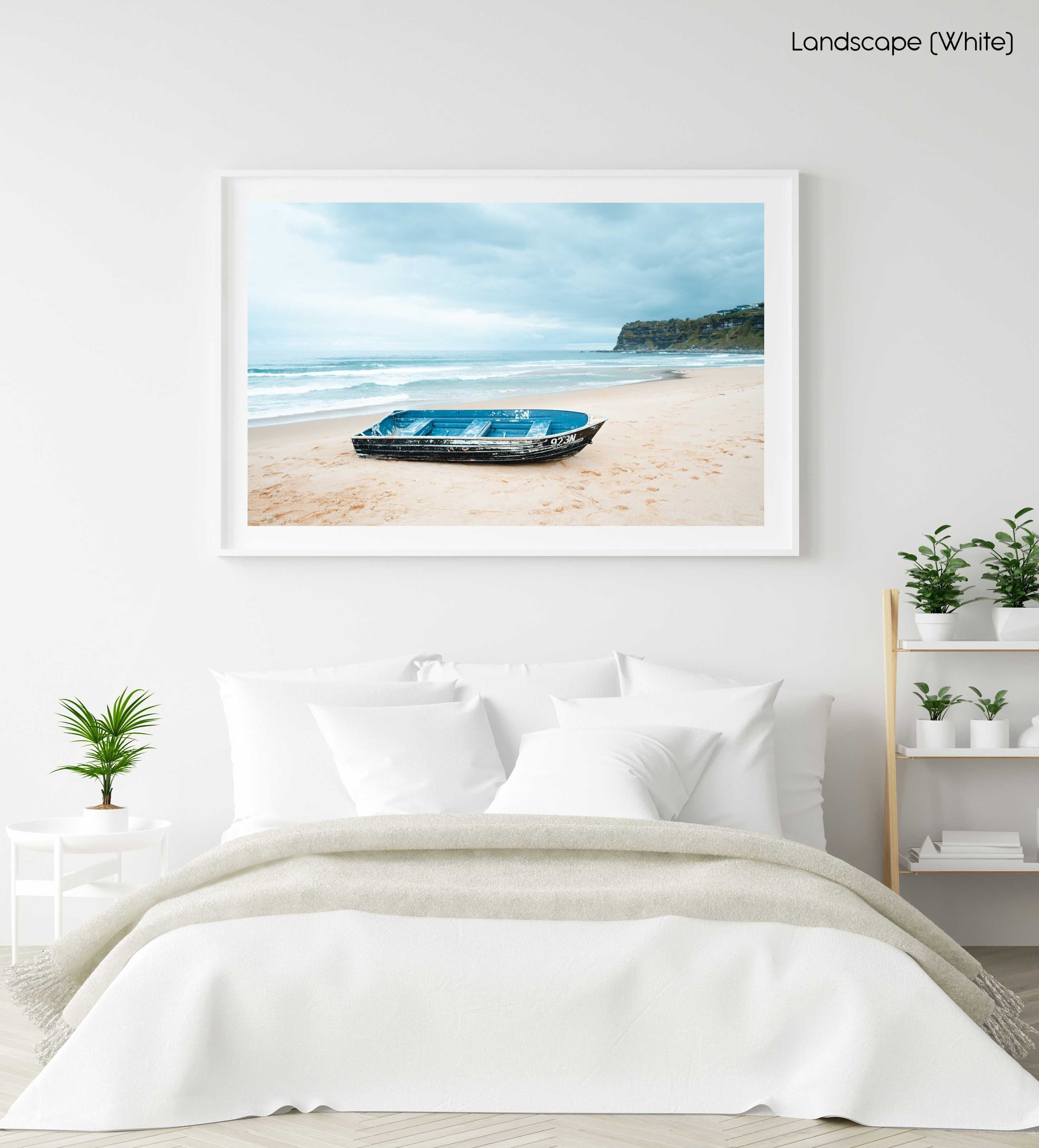Stranded blue boat on northern beaches on cloudy day in a white fine art frame