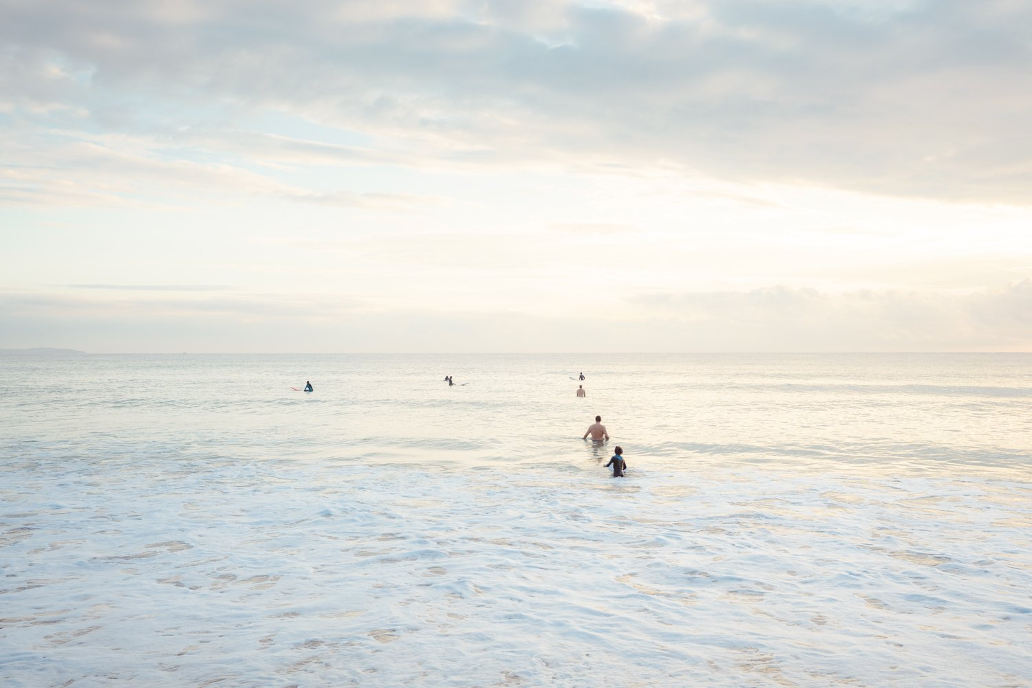 Neutral surfers lined up in water for sunrise surf on Manly Beach Sydney