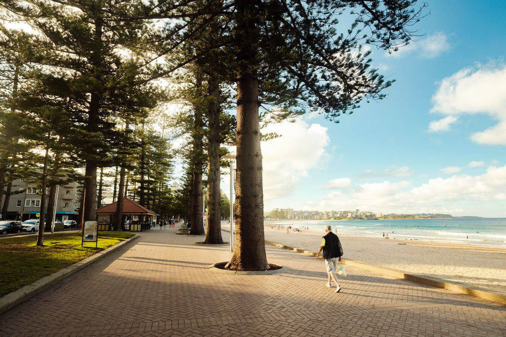 Old man walking along the promenade at Manly Beach in Sydney