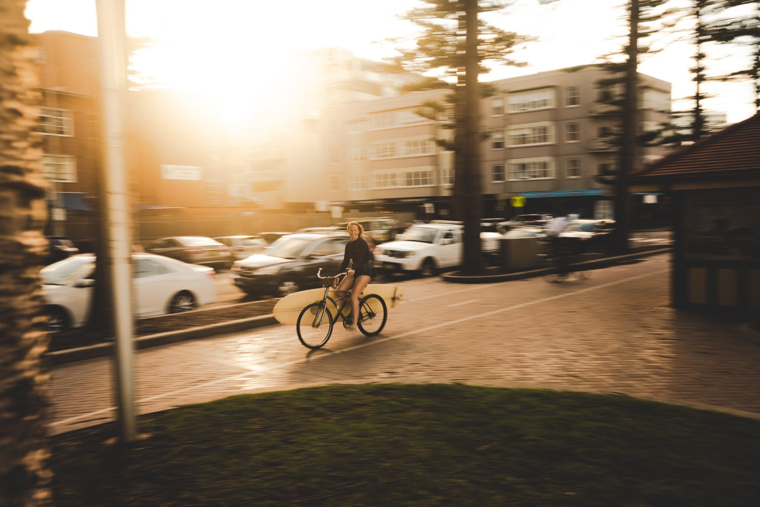 Girl riding bicycle with surfboard rack during sunset on promenade in Manly Sydney