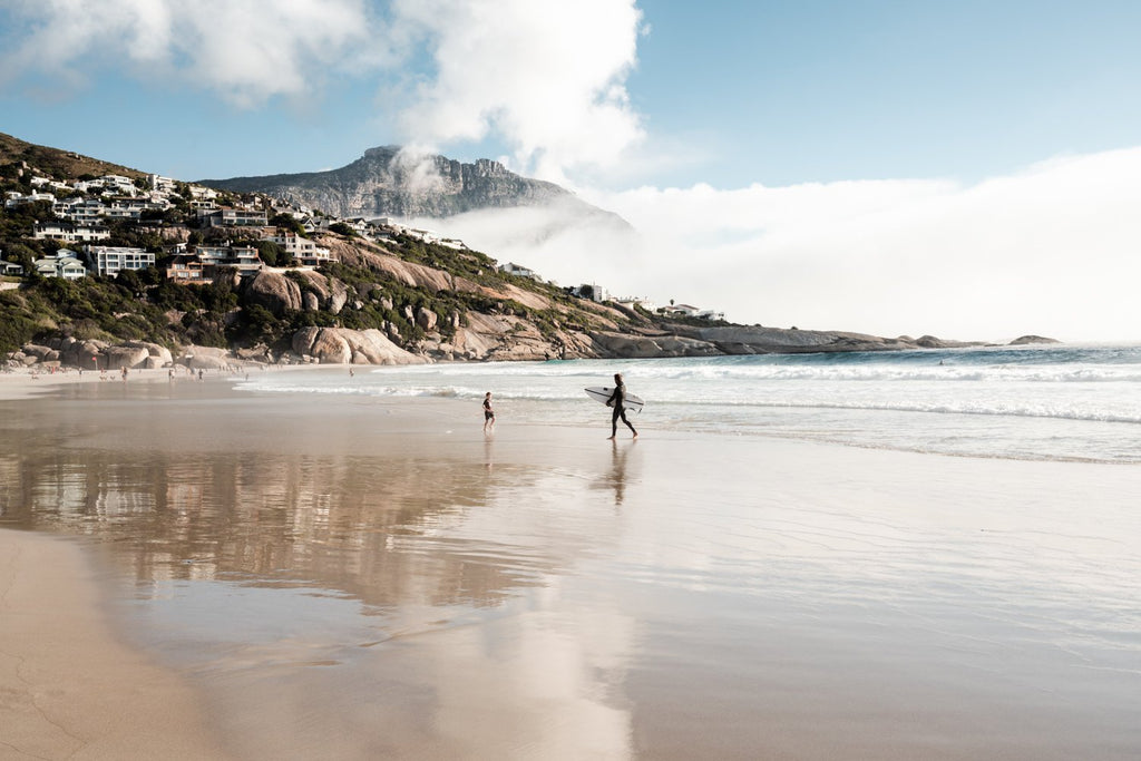 Surfer walking towards a kid on Llandudno Beach in Cape Town