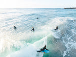 Aerial of bodyboarder surfing a wave amongst other surfers in Sandy Bay Cape Town
