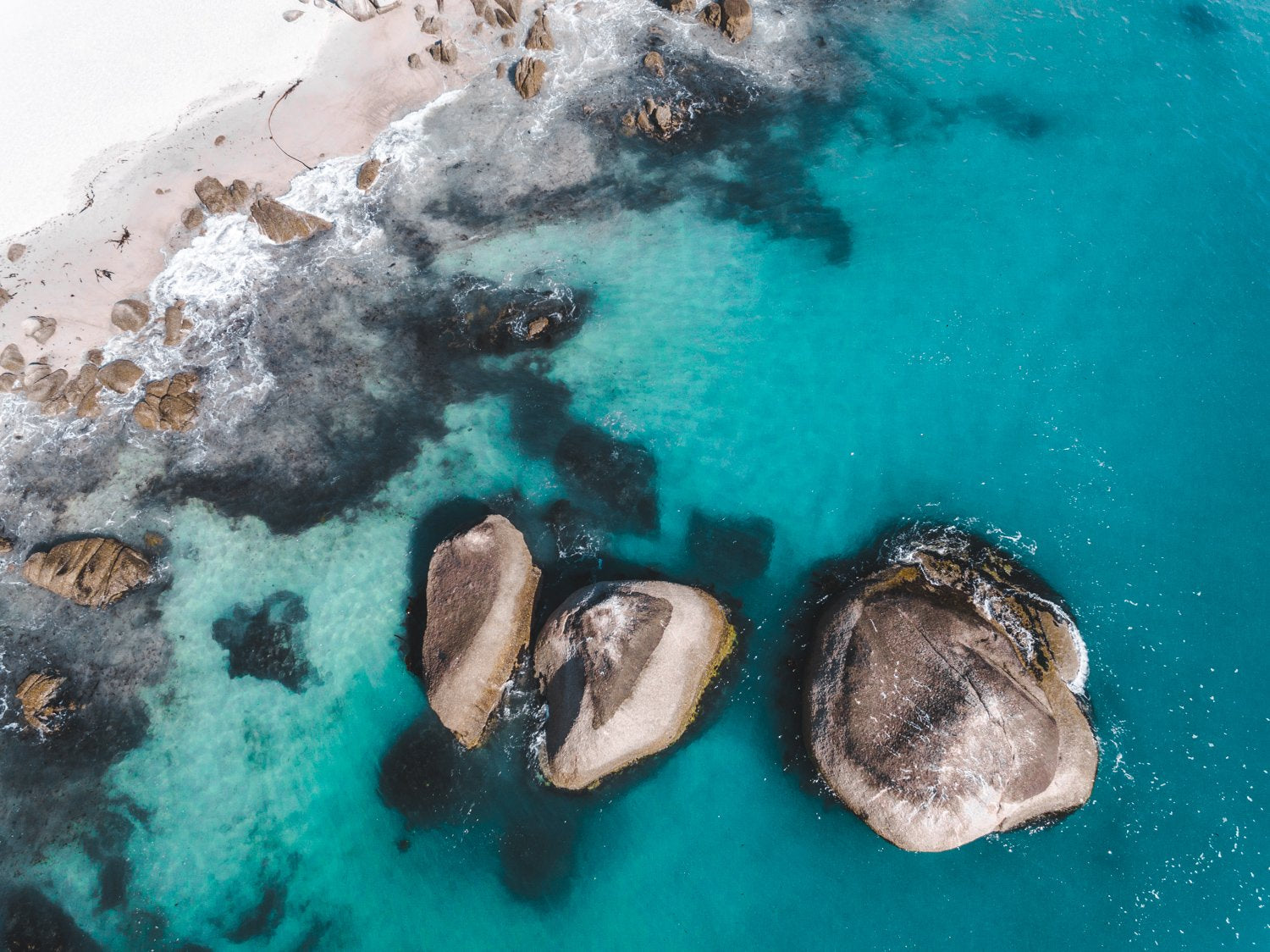 Aerial of three big boulders in blue Atlantic Sea in Clifton Cape Town