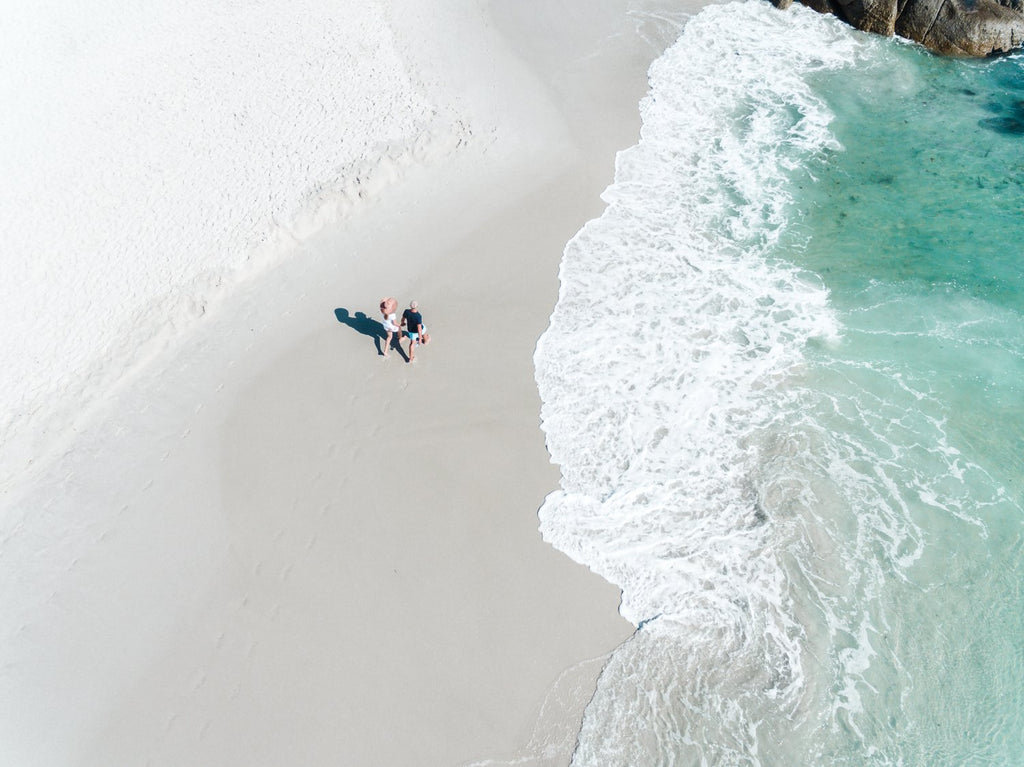 Aerial of a couple holding hands walking along Clifton Beach in Cape Town
