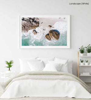 Girl standing among boulders on Clifton beach from above in a white fine art frame
