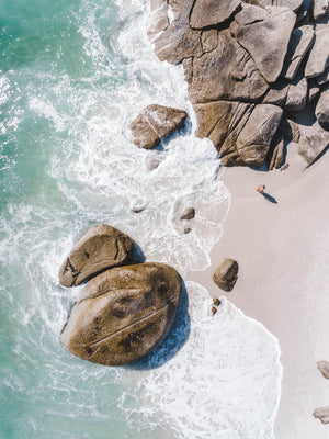Girl standing among boulders on Clifton beach from above