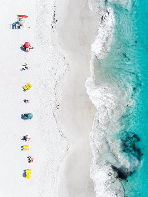 Aerial of colorful towels and umbrellas along blue sea on Clifton Beach Cape Town