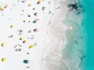 Colorful umbrellas, towels and people along white sand of Clifton Beach Cape Town