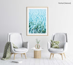 Blue ocean and seaweed with light shining on it in a natural fine art frame
