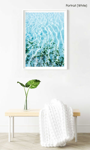 Blue ocean and seaweed with light shining on it in a white fine art frame