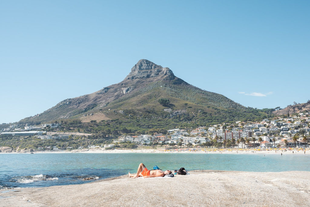 Old man lying on rock at Camps Bay beach below lions head