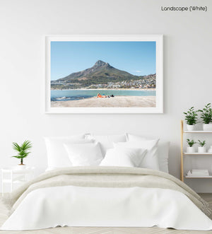 Old man lying on rock at Camps Bay beach below lions head in a white fine art frame