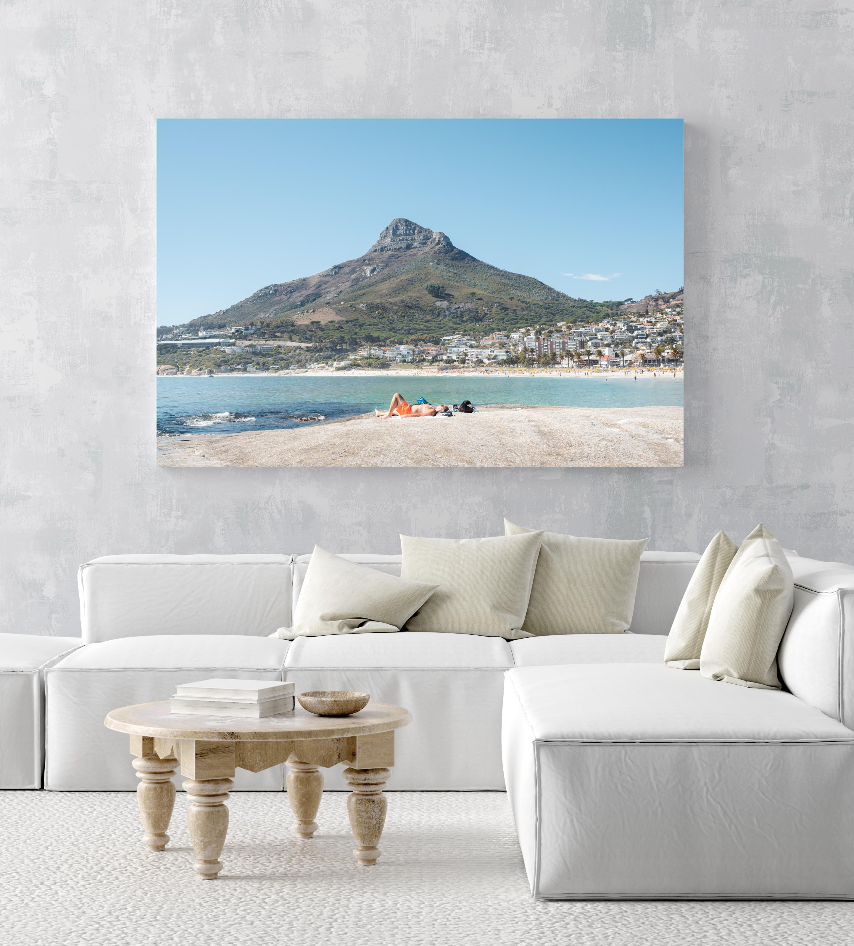 Old man lying on rock at Camps Bay beach below lions head in an acrylic/perspex frame