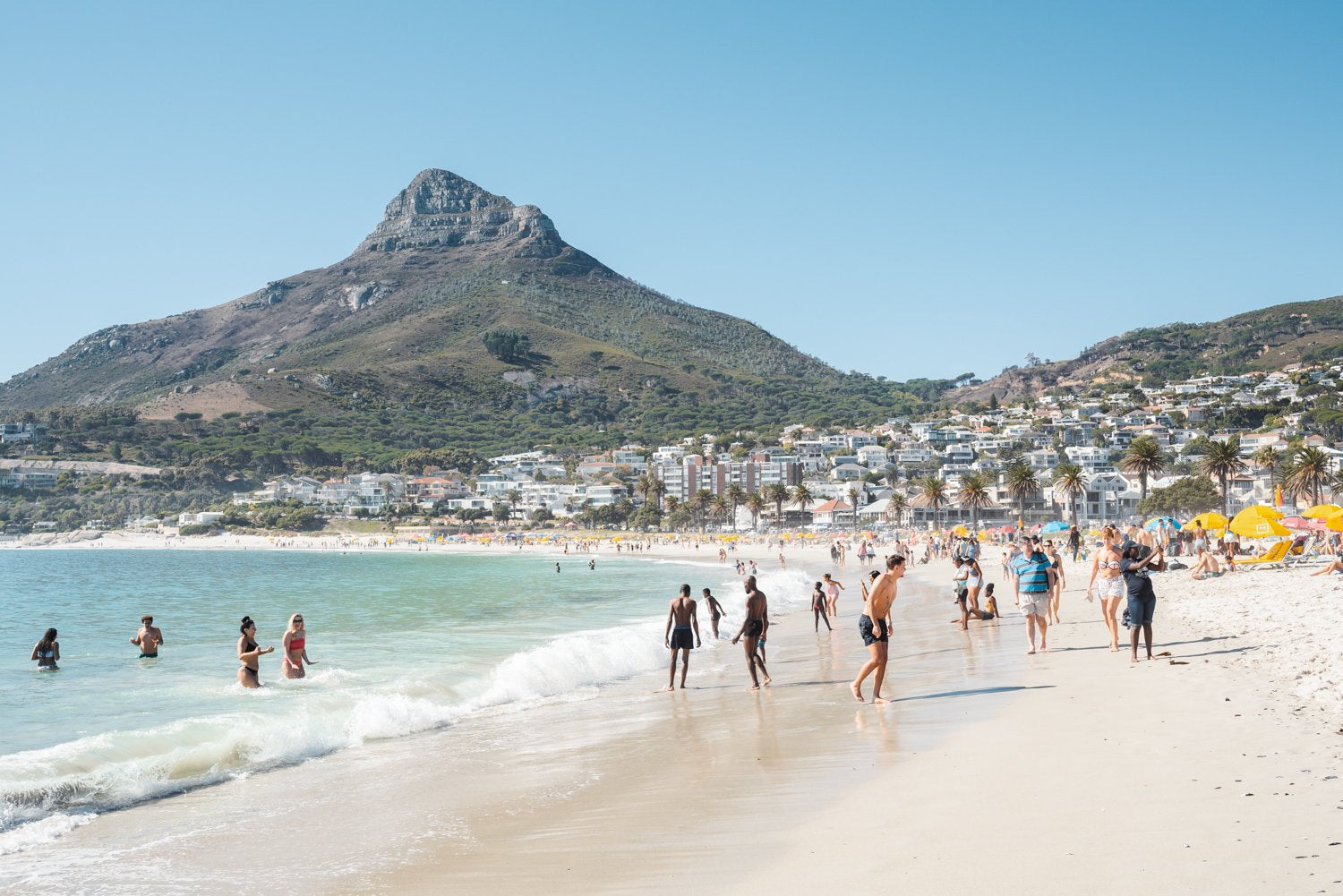 People swimming and playing on Camps Bay Beach below the lions head