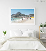 People swimming and playing on Camps Bay Beach below the lions head in a white fine art frame