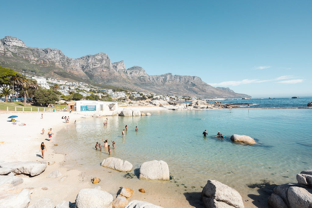 People swimming in the blue tidal pool in Camps Bay Cape Town