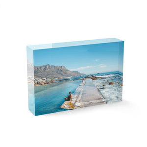 Man sitting along edge of Camps Bay pool with twelve apostles mountains in background