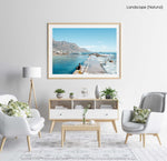 Man sitting along edge of Camps Bay pool with twelve apostles mountains in background in a natural fine art frame