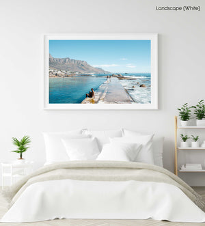Man sitting along edge of Camps Bay pool with twelve apostles mountains in background in a white fine art frame