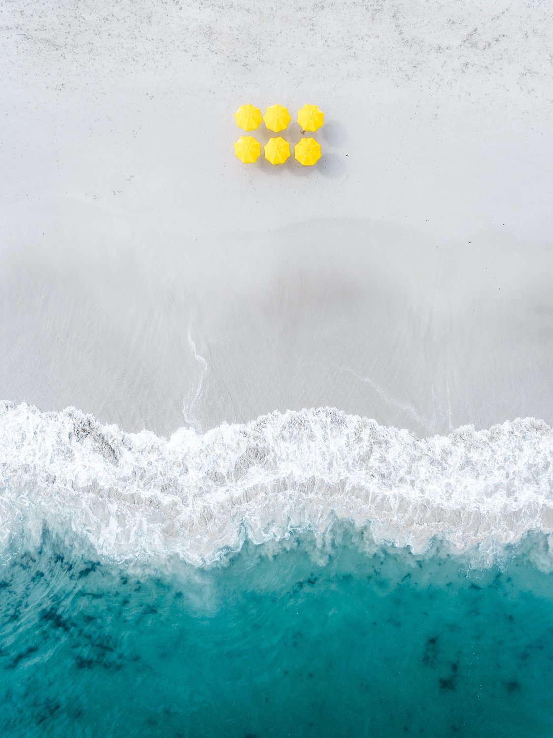 Aerial of six yellow umbrellas next to blue ocean on Camps Bay beach in Cape Town