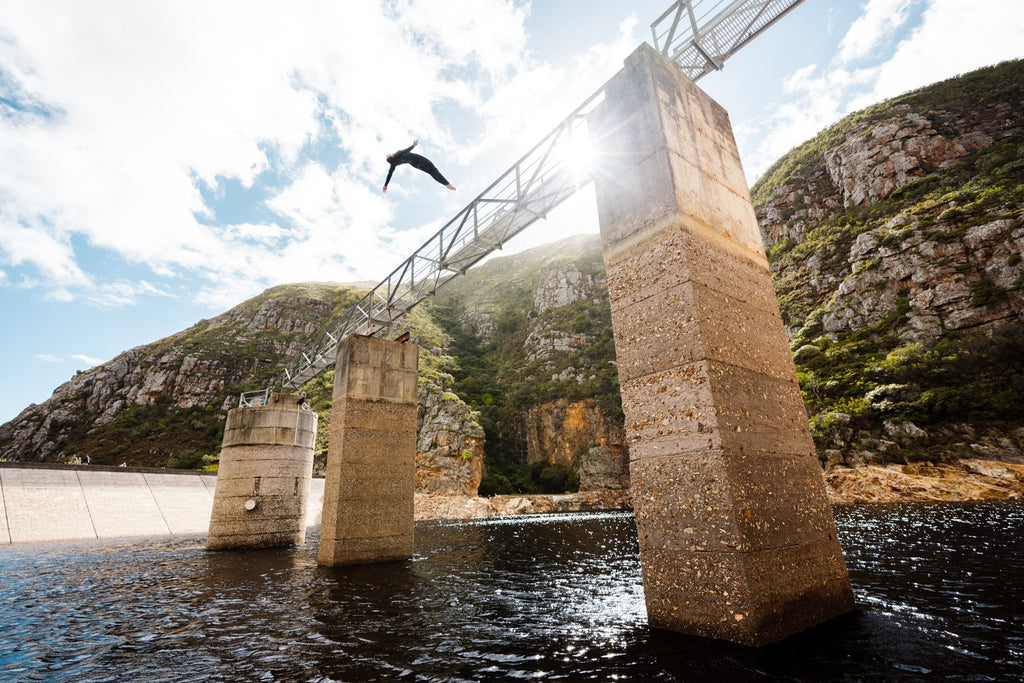 Boy doing a backflip off a bridge at Hermanus dams South Africa