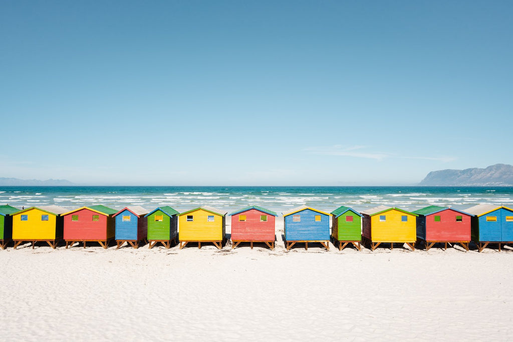 A row of colorful huts along Muizenberg Beach