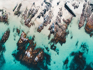 Rock slabs from above along the coast of Kalk Bay in blue calm water