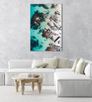 Rock slabs along the coast of Kalk Bay in blue calm water in a natural fine art frame