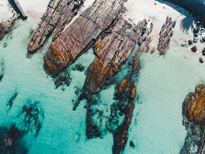 Aerial of rock slabs along the coast of Kalk Bay in blue water