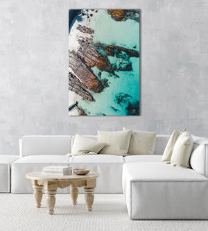 Rock slabs along the coast of Kalk Bay in blue water in a natural fine art frame