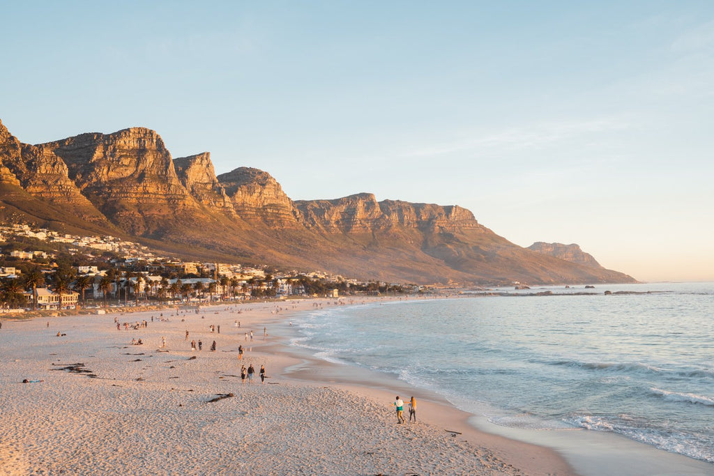 People walking along Camps Bay beach during an orange sunset