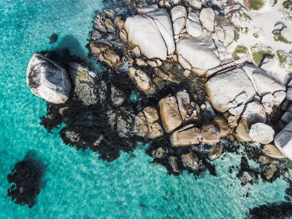Aerial of boulders and blue sea along the coast of Simons Town