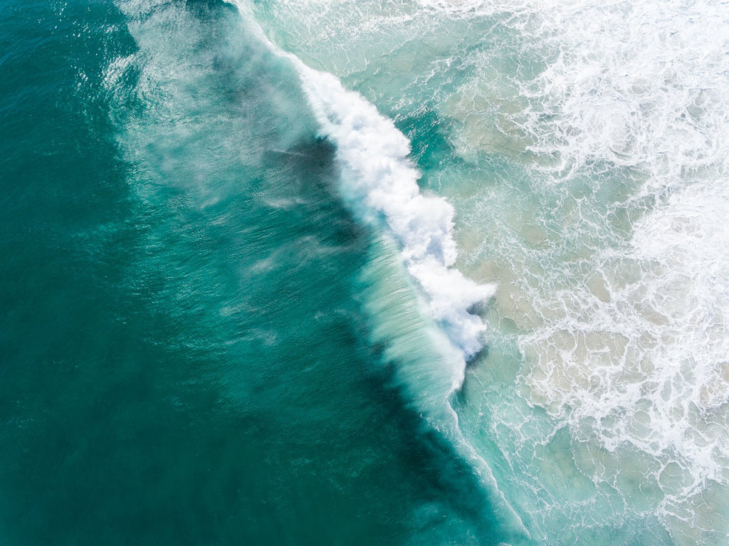 Big wave breaking in dark turquoise Noordhoek Beach from the air